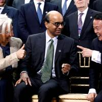Just add liquidity!: IMF Managing Director Christine Lagarde jokes with IMF Committee Chair Tharman Shanmugaratnam (center) and Finance Minister Taro Aso before a photo at the World Bank IMF Spring Meetings in Washington on April 20. | AP