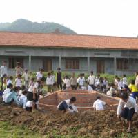 Base for hope: Children build a base for their new school's flagpole in Pailin Province, Cambodia.   COURTESY OF AMATAK HOUSE OF CAMBODIA