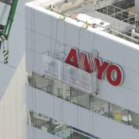 End of a giant: The Sanyo logo is removed letter by letter from the new Panasonic unit's headquarters in Osaka on Friday. | KYODO
