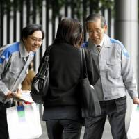 Leaving your lights on?: Kyushu Electric Power Co. officials hand out leaflets urging consumers to cut power usage by 5 percent in front of JR Hakata Station in Fukuoka on Monday. | KYODO PHOTO
