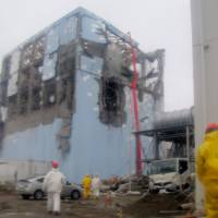 Close to the action: Workers wearing protective suits monitor water being sprayed during a cooling operation at the damaged No. 4 reactor at the Fukushima No. 1 power plant in this March 22 photo released by Tokyo Electric Power Co. | TEPCO/AP