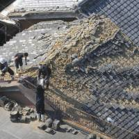 Workmen in Sumoto, Hyogo Prefecture, remove shingles from a roof damaged by the 6M quake that struck western Japan early Saturday morning. | KYODO