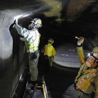 Just in case: Workers check inside the Enasan Tunnel in Nagano Prefecture on Monday, following the deadly collapse of the concrete ceiling of the Sasago Tunnel in Yamanashi Prefecture on Sunday. | KYODO