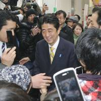Short-term gain?: Liberal Democratic Party chief Shinzo Abe is surrounded by voters after making a speech on his party's economic policies in Tokyo on Nov. 24. | KYODO