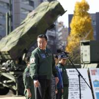 Launch-ready: Prime Minister Yoshihiko Noda, standing by a ground-based Patriot Advanced Capability-3 interceptor battery, looks back as he speaks Friday during an inspection tour to the Defense Ministry in Tokyo. | AP