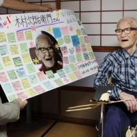 For record longevity: Jiroemon Kimura is offered a board with congratulatory messages from local elementary school pupils at his home in Kyotango, Kyoto Prefecture, in September. | CITY OF KYOTANGO/KYODO