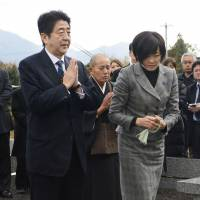 A time to pray: Incoming Prime Minister Shinzo Abe and his wife visit the grave of his father, former Foreign Minister Shintaro Abe, on Saturday in Nagato, Yamaguchi Prefecture.   KYODO
