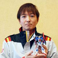 Toys for men: Junichi Nishizawa, one of the model makers at Bandai Co., holds a plastic rendering of the popular Gundam character in November. | KYODO