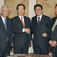 In agreement: Incoming Prime Minister Shinzo Abe, leader of the Liberal Democratic Party (third from right), and New Komeito leader Natsuo Yamaguchi seal their deal Tuesday at the Diet. The two leaders of the coalition partners signed a policy agreement the same day.   KYODO