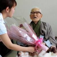 Milestone: Jiroemon Kimura receives flowers Friday at a hospital in Kyotango, Kyoto Prefecture, after he became the world's longest-lived man, reaching the age of 115 years and 253 days to top the previous Guinness record by a day. | KYODO