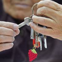Turnkey: A woman holds the key to a new public housing unit in the town of Yamamoto, Miyagi Prefecture, Monday. Her strawberry key chain reflects a specialty of the town. | KYODO