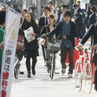 Dismount: People push their bicycles along a sidewalk designated as a 'walk zone' in the city of Fukuoka on Monday. | KYODO
