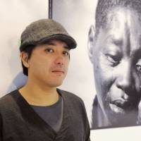Conflict zone: Ryo Kameyama stands near one of his photos during an exhibition in Tokyo in December. | KYODO