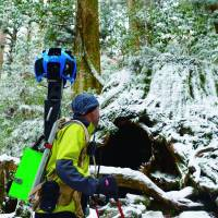 Viewfinder: With a special panoramic camera on his back, a Google employee treks across Yakushima Island in Kagoshima Prefecture in February to take images for the search engine's Street View service. Google says the views of the World Heritage site will be available online possibly by this summer. | GOOGLE INC./KYODO