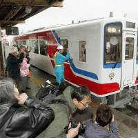 Back on track: A train on the Minami Riasu Line, which was devastated by the March 2011 earthquake and tsunami, pulls out of Sakari Station in Ofunato, Iwate Prefecture, on Wednesday for the first time in more than two years. | KYODO