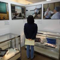 A healer's story: A visitor takes in an exhibit on March 15 at Kumamoto Gakuen University's Open Research Center for Minamata Studies in Minamata, Kumamoto Prefecture. | KYODO