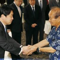 Touch and go: Visiting Defense Minister Itsunori Onodera (left) is greeted by Okinawa Gov. Hirokazu Nakaima in Naha prior to talks Saturday on the return of land used by the U.S. military. | KYODO