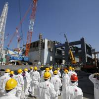 Radioactive route: Journalists in protective gear are taken to the No. 4 reactor building at the Fukushima No. 1 nuclear plant on March 6. | AP