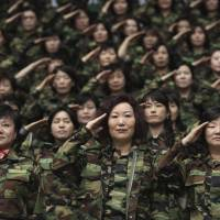 Ready to move out: South Korean Army reservists salute during a ceremony at a gymnasium in Seoul on Friday.   AP