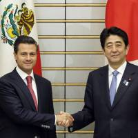 Grip and grin: Prime Minister Shinzo Abe (right) and Mexican President Enrique Pena Nieto pose at Abe's official residence in Tokyo on Monday. | POOL