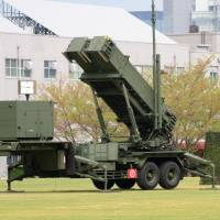 Armed and ready: An Air Self-Defense Force airman walks past a Patriot Advanced Capability-3 missile launcher deployed outside the Defense Ministry on Wednesday. | AFP-JIJI