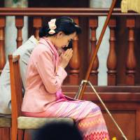 Homecoming: Myanmar opposition leader Aung San Suu Kyi prays before she delivers a speech Monday at Ryukoku University in the city of Kyoto. | KYODO
