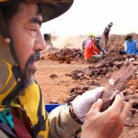Mining for clues: Yoshikazu Noda, a researcher at the Fukui Prefectural Dinosaur Museum, holds a fossil excavated at a site in Nakhon Ratchasima Province, Thailand, on Feb. 4 through a joint project with the Khorat Fossil Museum. | KYODO