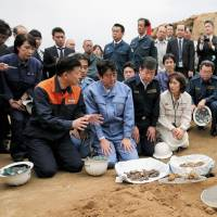 Prime Minister Shinzo Abe inspects work to recover the remains of Imperial Japanese Army soldiers killed in the Battle of Iwojima during his visit to the island Sunday. | KYODO