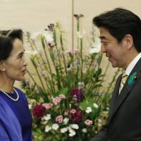 Hi: Nobel laureate and Myanmar opposition leader Aung San Suu Kyi and Prime Minister Shinzo Abe exchange greetings ahead of their meeting at the prime minister's office on Thursday. | AFP-JIJI