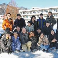 Moving in: Carl Sundberg (first row, fourth from left) and some of his employees pose in the playground of a former school in Aizumisato, Fukushima Prefecture, on Jan. 24. | KYODO