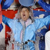 Victorious: Supporters of Nagoya Mayor Takashi Kawamura dump a celebratory bucket of water on him Sunday after deciding from early returns that their bicycle-riding tax cutter had won re-election. | KYODO