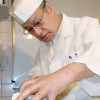 In the best tradition: Eiichi Takahashi, the 14th generation head chef at Hyotei, a traditional restaurant in Kyoto, prepares a fish March 1. | KYODO