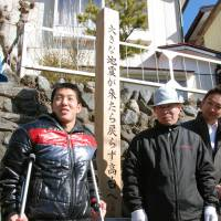 Message to the future:  Yusaku  Yoshida (left), a 16-year-old high school student in Otsuchi, Iwate Prefecture, and Tadayoshi Oguni, deputy chief of the Ando district neighborhood association, stand in front of a wooden monument Yoshida erected on a hill in Otsuchi on March 11. | KYODO