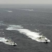 Rocking the boat: Ships from China's State Oceanic Administration, the Japan Coast Guard and boats carrying members of a Japanese nationalist group sail in Japanese territorial waters around the Senkaku Islands on Tuesday morning. In the foreground, a Japan Coast Guard cutter stays between a Chinese vessel at left and a boat carrying the nationalists. | KYODO