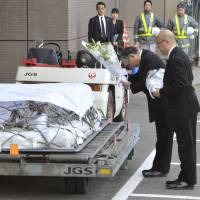 The war goes on: Koichi Kawana (right), president of engineering firm JGC Corp., and another JGC official place flowers on the coffins of fellow employees killed by terrorists in Algeria in January. A government panel is to submit proposals Friday to increase compensation for those caught up in terrorist attacks abroad.   KYODO