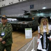 Real cyberworld: A 'cosplayer' poses with a Ground Self-Defense Force member and its main battle tank during the Nico Nico Chokaigi event Saturday at Makuhari Messe in Chiba. | KAZUAKI NAGATA