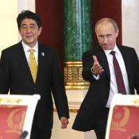 The final word: Prime Minister Shinzo Abe and Russian President Vladimir Putin approach the podiums before holding a joint news conference at the Kremlin in Moscow on Monday. | AP