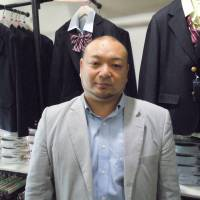 Takayuki Aiura, president of CONOMi, stands in front of racks of fake uniforms at his store in the Harajuku district of Tokyo in mid-April. | TOMOHIRO OSAKI