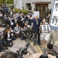 Victorious: Akio Mizoguchi, who sued the government for failing to recognize his deceased mother as a victim of Minamata disease, waves to supporters Tuesday outside the Supreme Court.  | KYODO