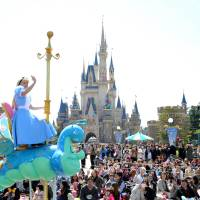 The show goes on: Visitors watch a parade Thursday at Tokyo Disneyland in Urayasu, Chiba Prefecture. | YOSHIAKI MIURA