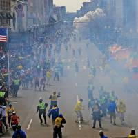 Sudden impact: People react as a bomb explodes Monday near the finish line of the 2013 Boston Marathon.  Two explosions went off near the finish line, sending authorities out onto the course to carry off the wounded while the stragglers were rerouted away from the smoking site of the blasts.  | AP