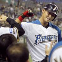 Team spirit: Hokkaido Nippon Ham's Sho Nakata (right) is congratulated by teammate Keiji Obiki after slugging a third-inning solo home run against the Tohoku Rakuten Golden Eagles on Wednesday at Tokyo Dome. The Fighters won 6-0. | KYODO