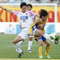 Close control: Sagan Tosu's Yohei Toyoda (left) controls the ball ahead of Vegalta Sendai's Shingo Tomita during their 1-1 draw on Sunday. | KYODO