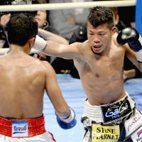 Heat of battle: Koki Kameda throws a punch against Thailand's Panomroonglek Kaiyanghadaogym during their WBA bantamweight title fight in Osaka on Sunday. | KYODO