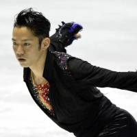 Grabbing the spotlight: Daisuke Takahashi performs in the men's free skate on Friday at the World Team Trophy at Yoyogi National Gymnasium. Takahashi finished first with 249.52 points. | KYODO