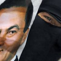 The good old days?: An Egyptian woman holds a poster of ousted President Hosni Mubarak during a demonstration outside the Supreme Administrative Court in Cairo on Monday.  The court says it does not have jurisdiction to rule on a case launched by supporters of Mubarak who challenged the legality of his removal from power two years ago. | AP