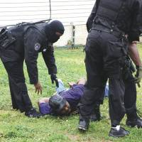 Busted: Narcotics agents arrest a man in Mississippi on March 14, 2012. He was later charged with selling crack cocaine. Eugene Jarecki, in his documentary 'The House I Live In,' notes that while just 13 percent of crack cocaine users in the U.S. are black, black Americans make up 90 percent of those imprisoned for crack-related crimes.   AP