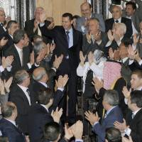 Still standing: Syrian President Bashar Assad waves as he greets lawmakers before a March 2011 speech to Parliament.   AP