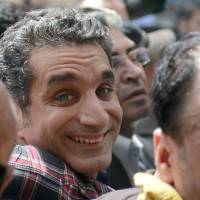 Reason to smile: Egyptian satirist and television host Bassem  Youssef is surrounded by supporters upon his arrival at the high court public prosecutor's office at the high court in Cairo on March 31.   AFP-JIJI