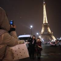 Easy marks:  Tourists take pictures near the landmark Eiffel Tower in Paris on March 30. | AFP-JIJI